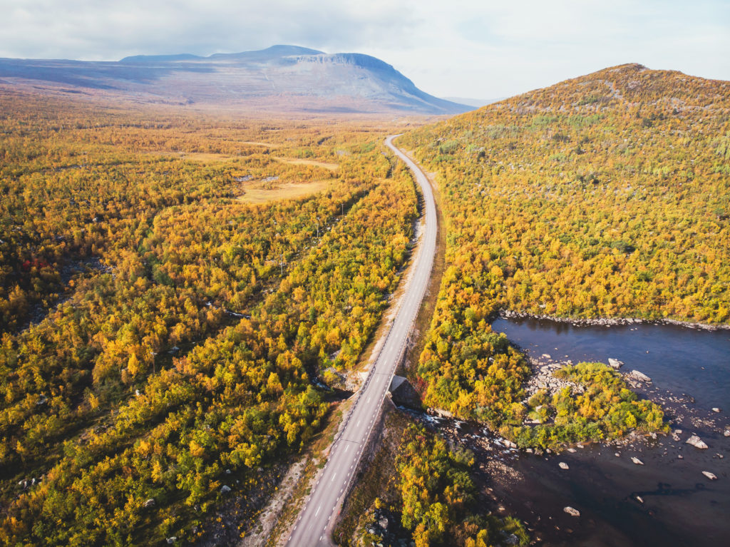 Aerial sunny fall autumn view of Abisko National Park, Kiruna Municipality, Lapland, Norrbotten County, Sweden, shot from drone, with Abiskojokk river, road and Nuolja mountai