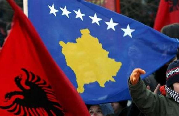 People celebrating with Kosovo and Albanian flags
