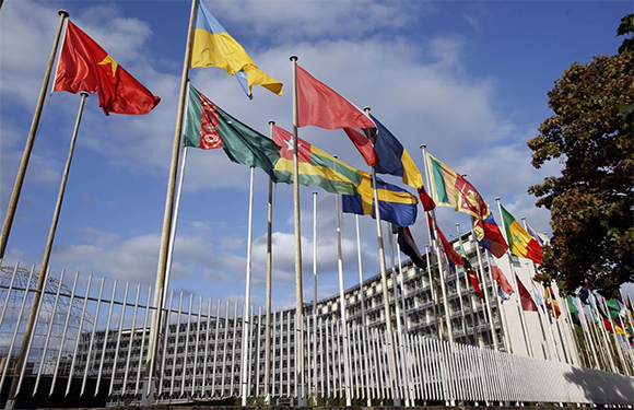 Flags from several countries float in front of the headquarters of the United Nations Educational